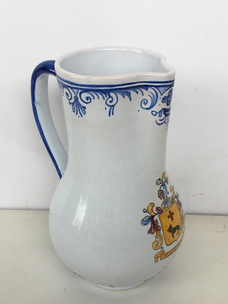 A striking Spanish glazed earthenware handled blue and white painted pitcher, the body underglaze blue decorated & heraldic shield  Talavera de la Reina pottery is a craft made in Talavera de la Reina, Toledo (Spain). Dishes, jars and other
