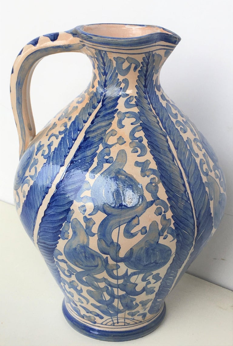 A striking Spanish glazed earthenware handled blue and white painted vessel, the body underglaze blue ornamental decorated .