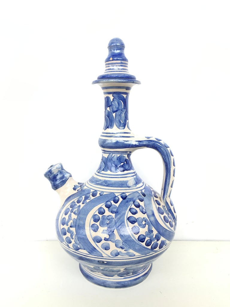 A striking Spanish glazed earthenware handled blue and white painted pitcher , the body underglaze blue ornamental decorated .