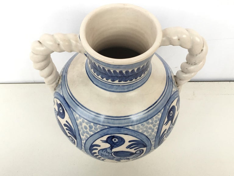 A striking Spanish glazed earthenware two-handled blue and white painted urn with foliate molded handles, the body underglaze blue ducks decorated very tipycal of this region.  Talavera de la Reina pottery is a craft made in Talavera de la Reina,