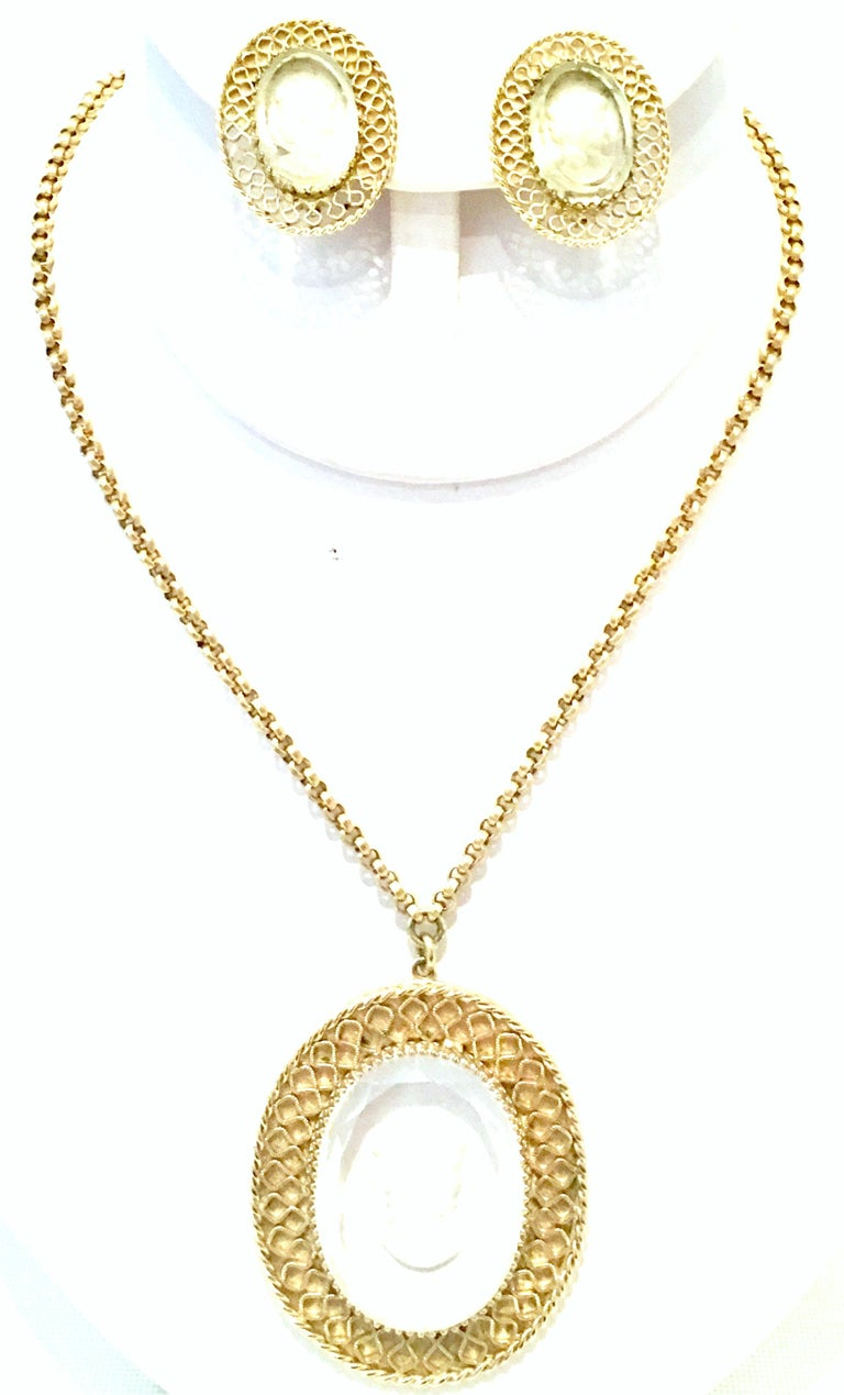 20th Century Gold Plate And Reverse Carved Art Glass Pendant Necklace And Earrings By, Whiting & Davis. This finely crafted three piece set features gold plate metal with fancy prong set translucent reverse carved glass cameo. The Clip style pair of