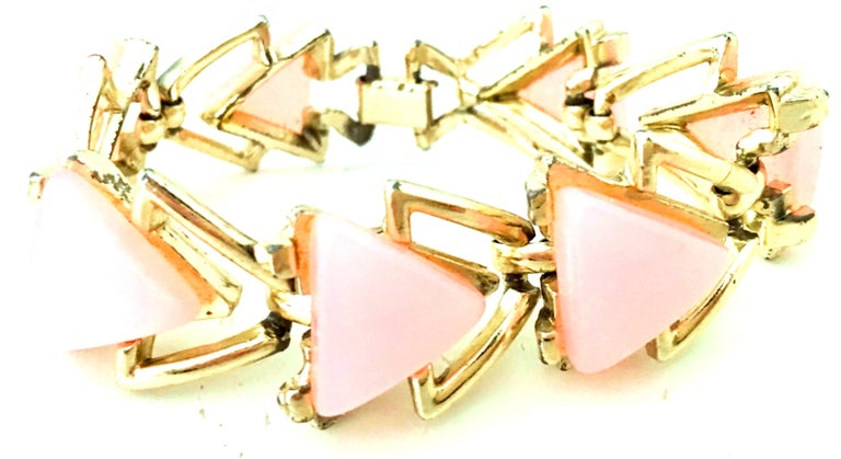 20th Century Gold & Pink Lucite Link Bracelet By, Coro. Features gold plat metal with six pink Lucite triangles and seven gold triangle links. Fold over box style locking clasp. Each pink Lucite triangle is approximately, .75
