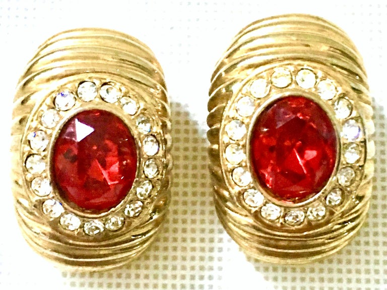 20th Century Gold & Swarovski Earrings By, Christian Dior. These classic and timeless earrings feature a curved and dimensional shape. Executed in gold plate metal with ridge detail and a large central ruby red cabochon stone surrounded by colorless