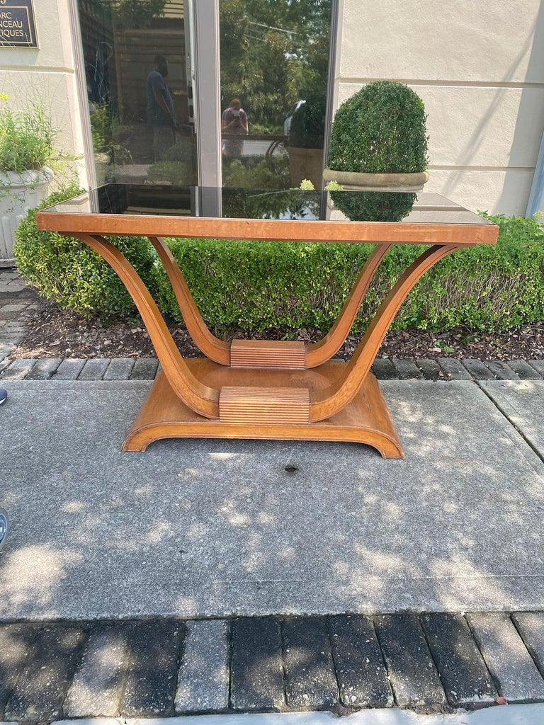 20th century Hollywood Regency mahogany console with inset black mirror glass and reeded supports.