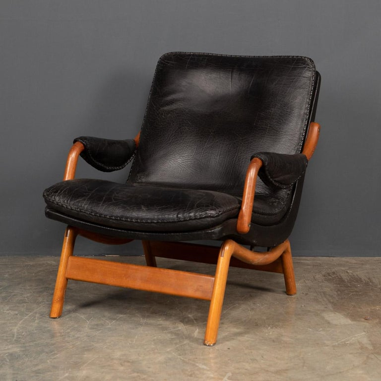 Very stylish chair, made by Ikea from the 1960's. This very comfortable chair has a teak frame and black leather seating with a good patination and a hand-stitch detail to the cushion.  Measures: Height: 84cm Depth: 90cm Width: 86m.