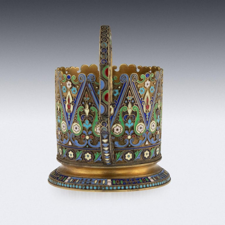 Antique early 20th century imperial Russian solid silver-gilt and cloisonné enamel tea glass holder, circular with upright scroll handle, shaped top rim and spreading foot, body profusely decorated with floral motifs in vary-colored cloisonné enamel