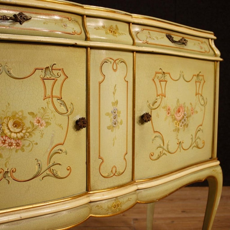 Venetian sideboard from 20th century. Furniture in lacquered, gilded and hand painted wood with floral decorations. Sideboard with two doors and two drawers of excellent proportion and service. Top in lacquered and painted wood. In good condition