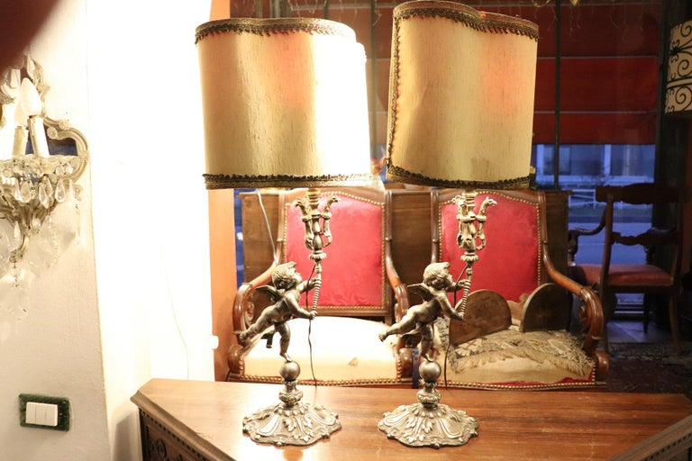 Pair of silvered bronze table lamp. The lamps are extremely refined, the forged bronze body is formed by figures of angels holding up the lamp. The lamps are working. The measures indicated are the maximum ones for the Lumen cap.
