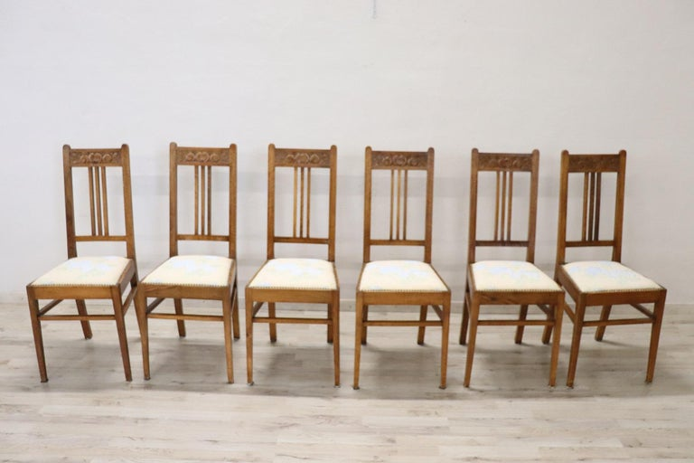 Series of six refined Art Nouveau Italian walnut wood chairs. Very simple and linear with floral decoration carved in the wood on the back. Perfect for a dining table. Beautiful chairs ready to be placed in your beautiful home.