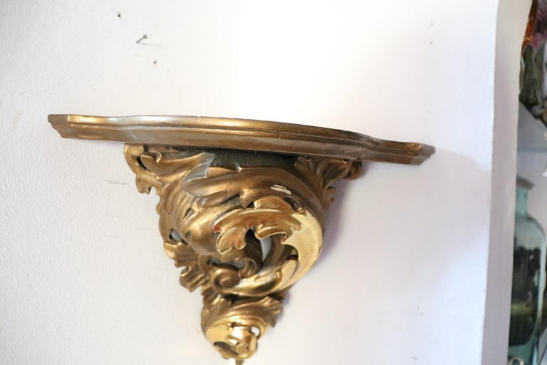 Rare Italian baroque style corner shelve 1850s in carved and gilded wood. The wood is finely carved with volutes and curls. Precious decoration in gold daughter. Perfect to make a corner of your home special.