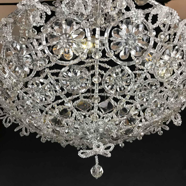 A stunning made in Italy chandelier with six lights and over thousands of crystal beads, strung and woven by hand to create flowers and floral patterns.  This unique and exclusive beaded crystal Italian chandelier is in good condition, it has been