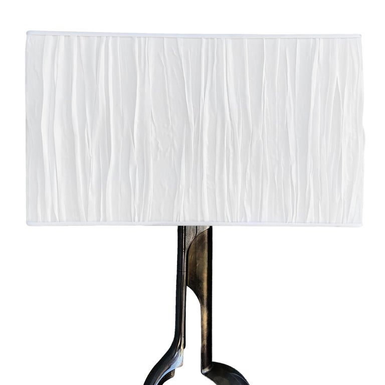A vintage Mid-Century Modern Italian chrome table lamp with a brass base. Featuring a one-light socket, in good condition. The wires have been renewed. Wear consistent with age and use, circa 1960, Italy.  Measures: Base 18
