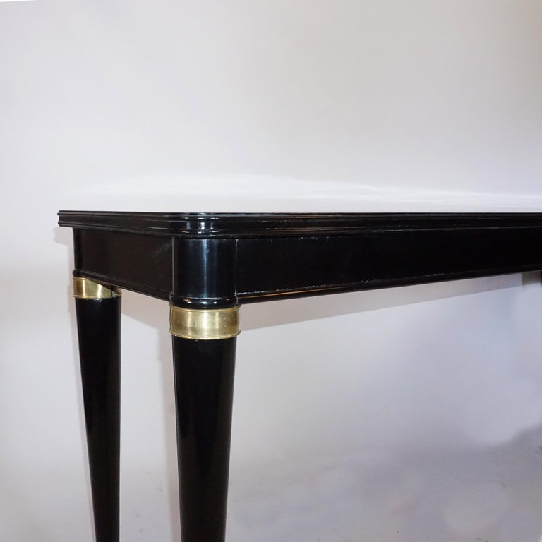 An Italian 20th Century ebonized console table in the style of Paolo Buffa with brass decor and fluted legs. Wear consistent with age and use. Circa 1940, Italy.  Paolo Buffa was an Italian architect and designer born in 1903 Milan, Italy and passed