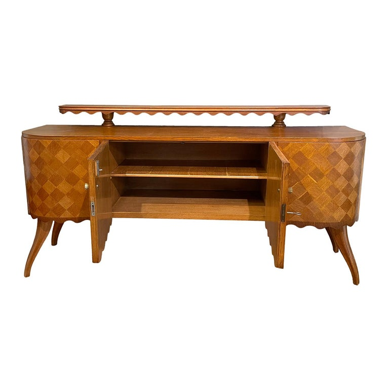 A light-brown, vintage Mid-Century modern Italian credenza made of hand carved Oakwood, shellac polished, semi-gloss with an upper shelf, standing on four curved wooden feet, designed by Paolo Buffa in good condition. The front is veneered in Oak