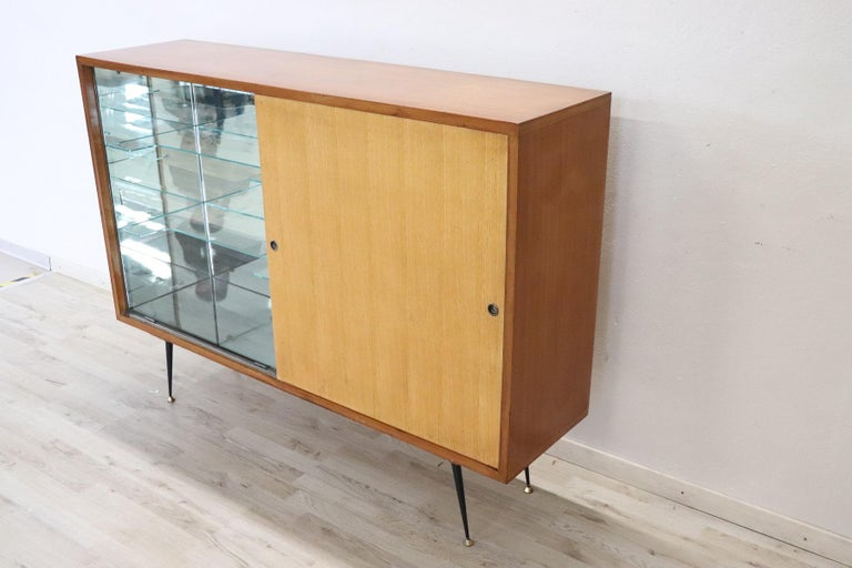 Beautiful and rare Italian design bar cabinet in teak, 1960s. One part has a bar cabinet with space for bottles with mirror. Perfect for a modern and young environment. Used good conditions.