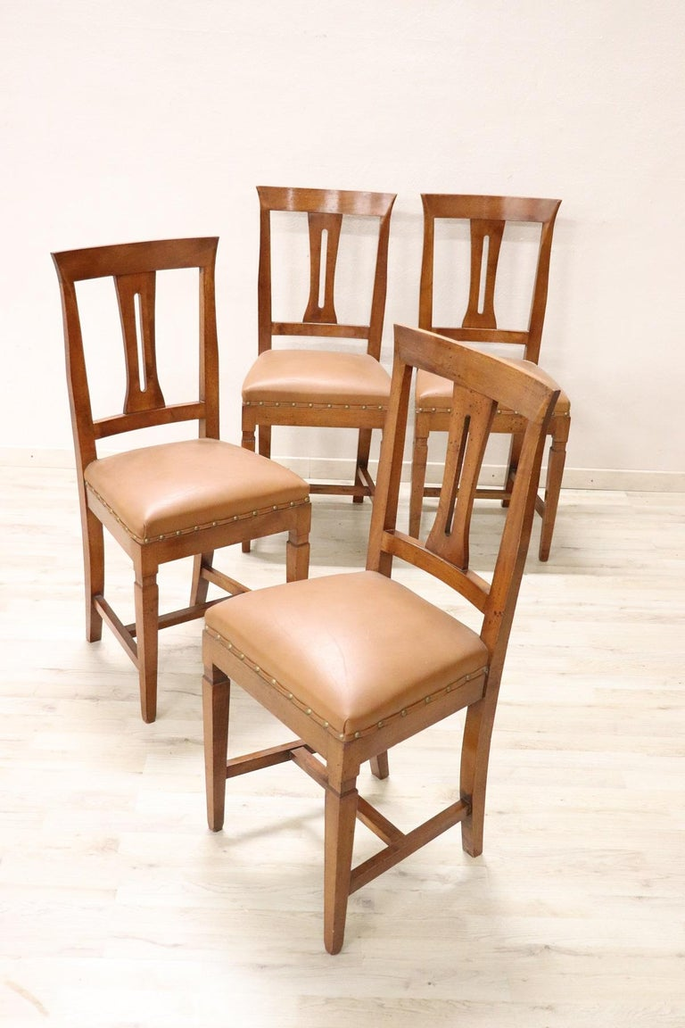Series of four refined Italian Louis XVI style four chairs in solid walnut wood. The legs are very elegant straight. The seat is wide and comfortable with light brown leather. The chairs are used good conditions. Please look good all the photos in