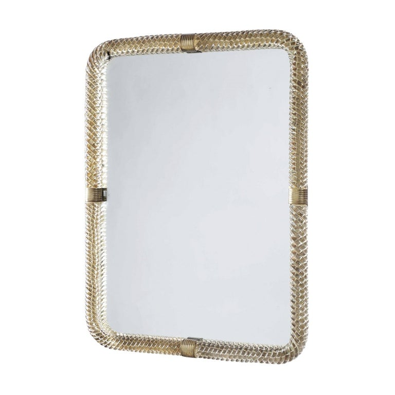 A vintage Mid-Century Modern Italian wall mirror made of hand blown Murano and mirrored glass with polished brass stripped rings. Produced by Barovier & Toso in good condition. Wear consistent with age and use. Circa 1940, Murano, Italy.  Barovier