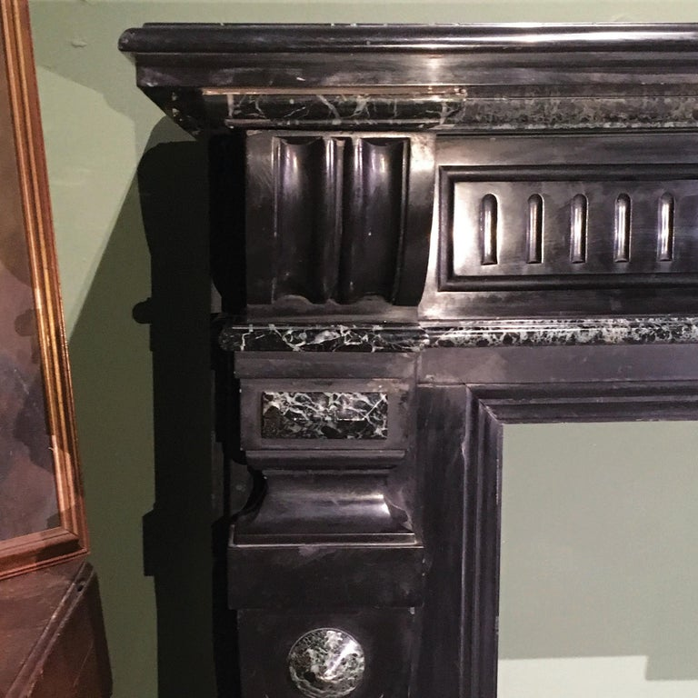 An elegant Tuscan marble fireplace from the early 20th century. The fireplace presents two beautiful qualities of marble - the Belgian black marble