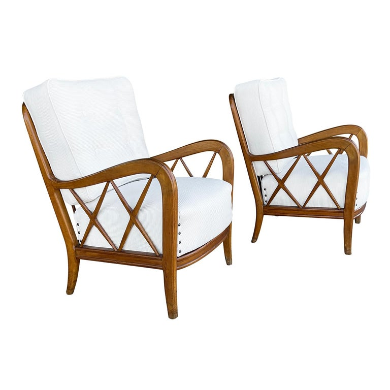 A vintage Mid-Century Modern Italian pair of armchairs made of hand carved Walnut. The backrest of the lounge chairs are spindled with X-form slats arms with a button-tufted back cushion and metal nailheads, standing on four wooden tapered legs.
