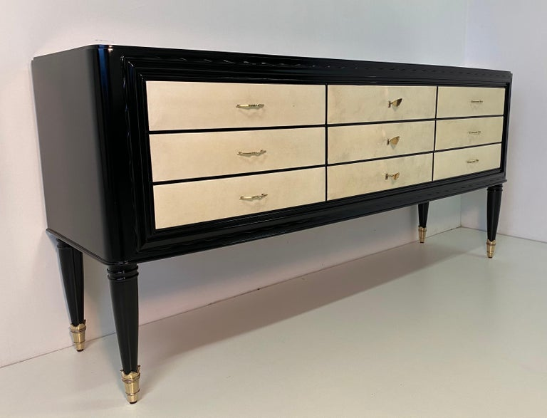 This chest of drawers was produced in Italy in the 1940s and is attributable to the design of Paolo Buffa. The structure is black lacquered while the drawers are covered with a precious parchment. The details and the handles are in