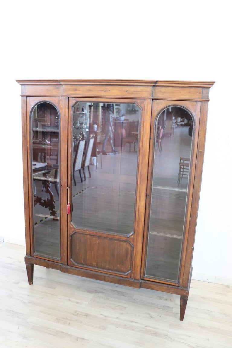Italian vitrine or bookcase about 1930s high quality furniture. Vitrine in poplar wood the line is very simple and linear. On the front three glass doors ideal for storing precious objects or your books. The distance of the internal shelves can be