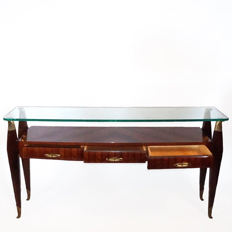 A vintage Mid-Century Modern Italian console table, Atelier di Varedo. Designed by Osvaldo Borsani in good condition. The legs are made of ebonized Mahogany and rosewood with detailed brass decor and three drawers, glass top. Wear consistent with