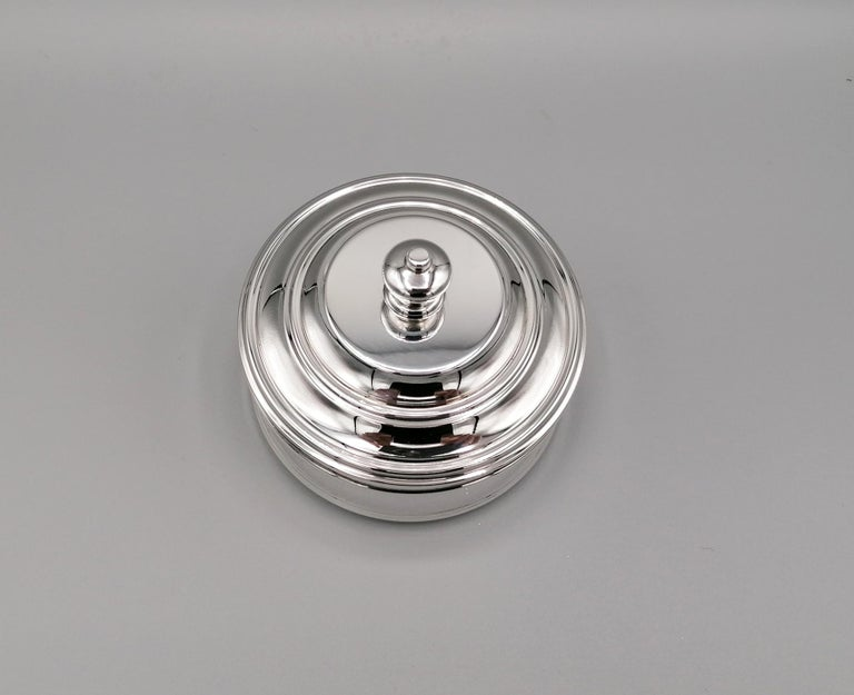 Round shape sterling silver jewelry box. The simplicity of the forms and the harmony of the proportions make it suitable for all settings. The lid of the jewelry box has a knob handle while the interior is lined with a precious blue fabric with a