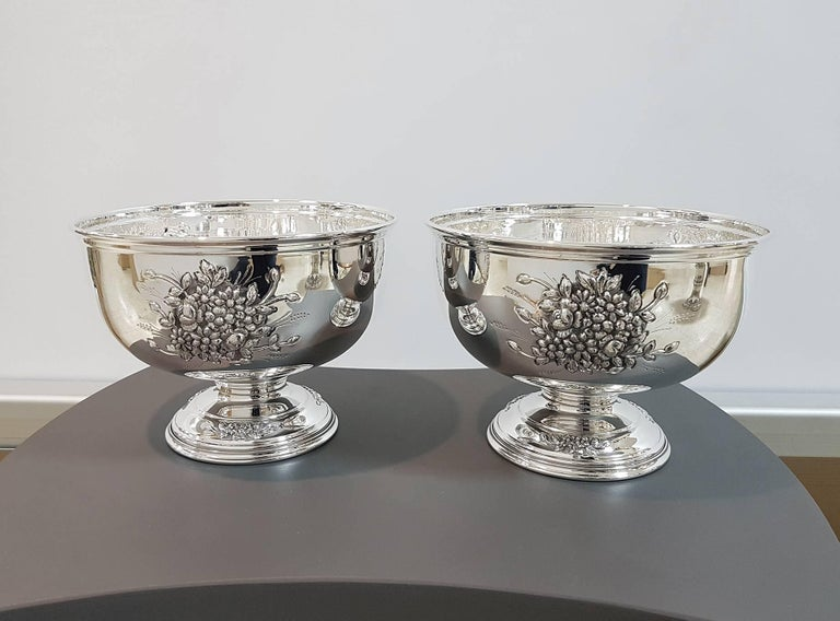 Pair of elegant solid silver 800 round centerpieces on base. The embossing and chisels with floral motifs are in three sectors, symmetrical both on the body and on the base. The centerpieces were made completely by hand.  2150 grams for both.