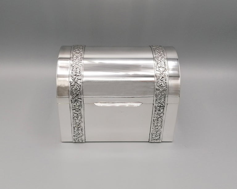 Jewelry box in solid 800 silver in the shape of a casket / trunk. The lid is hinged. The box is completely smooth with 2 bands shown and chiseled with leaf designs. The inside of the jewelry box is lined with dark red velvet. Weight 905