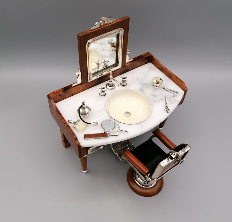 Extraordinary miniature representing the barber shop. The structure is in briar and the details (comb, brush, mirror, taps, scissors, etc.) are in 925 silver. The tabletop is in Carrara marble. The chair and washbasin are in enameled 925