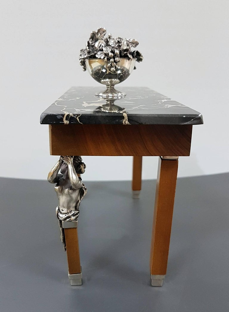 The table is sterling silver with marble top and structure in precious wood. The figures, the friezes and the fruit basket are in sterling silver  270 grams of solid silver.