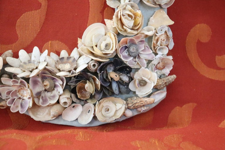 Italian artistic photo frame made entirely with small shells. The shells have been positioned so as to create many small flowers. Glued on cardboard. Sold in the conditions as photos do not have glass and wall hooking. Possible some small missing