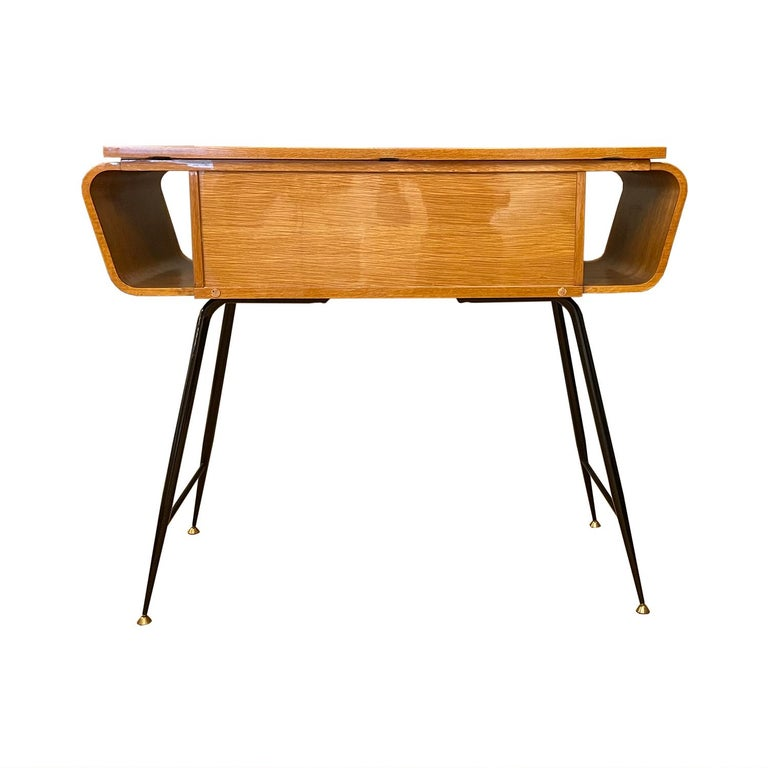 A vintage Mid-Century Modern Italian console table with two small, push out drawers, made of hand carved lacquered veneered Walnut, in good condition. The side, free standing table is standing on four curved metal, brass spider legs, designed by Ico