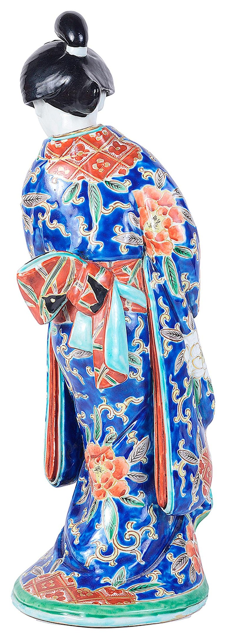 A good quality early 20th century Imari porcelain figure of a Geisha, having a wonderfully exotic colored kimono.