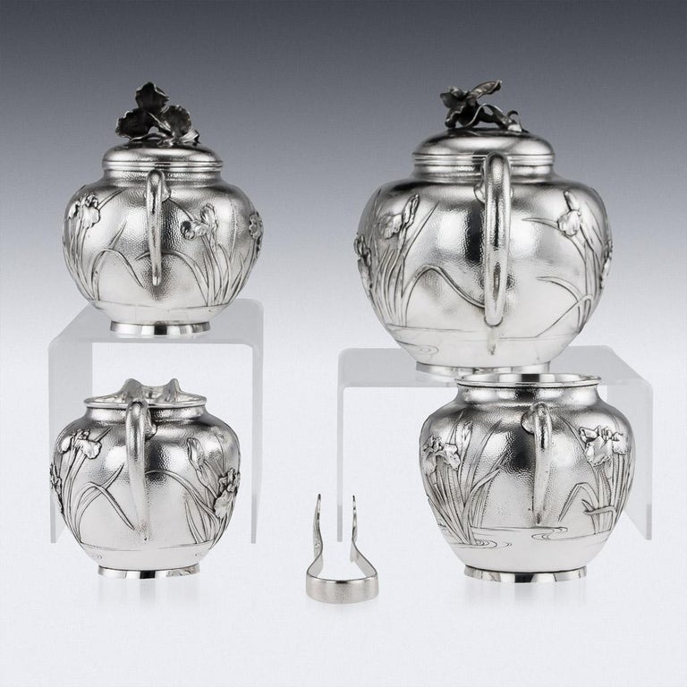Antique early 20th century Japanese solid silver five-piece tea set, consisting of a teapot, sugar bowl, waist bowl, cream jug and sugar tongs, exceptional quality, double walled, embossed with Iris flowers in water in high relief, C-form handles