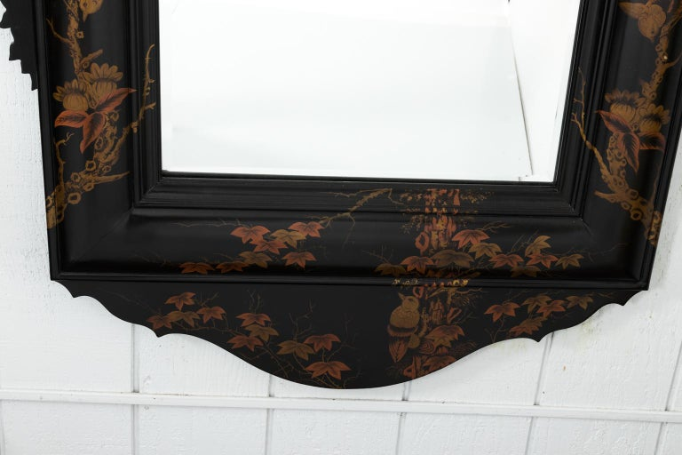 Japanned mirror with foliage and birds painted on an ebonized wooden frame with scalloped pediment, circa 20th century.
