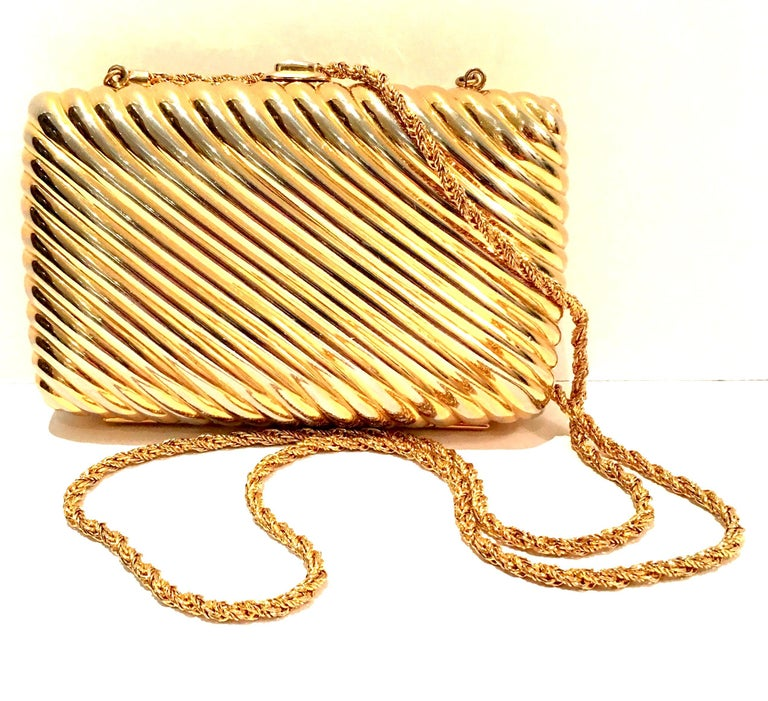 Classic & Timeless Judith Leiber gold gilt metallic metal hard case ribbed minaudière clutch or shoulder bag. Simple gold snap closure and gold chain shoulder strap (detachable). Gold metallic leather lining. Signed interior gold metal plaque