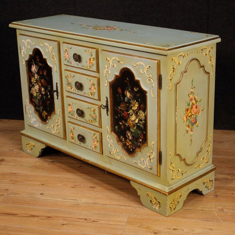 20th century Italian sideboard. Furniture of particular construction pleasantly lacquered, gilded and hand painted with floral decorations. Sideboard with two side doors and four central drawers of good capacity. Wooden top of good quality and
