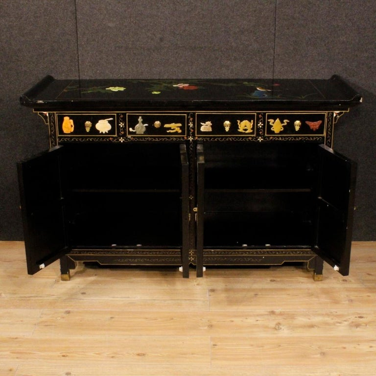 Chinese sideboard from 20th century. Furniture in carved, lacquered, painted wood and adorned with relief decorations in soapstone. High-quality sideboard of good service, equipped with four drawers and four doors. A drawer and a door have a lack of