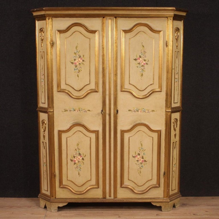 Italian wardrobe from 20th century. Furniture in carved, lacquered, gilded and hand painted wood with very pleasant floral decorations. Entrance cabinet with two doors, internally equipped with four chiseled metal hangers placed frontally on a