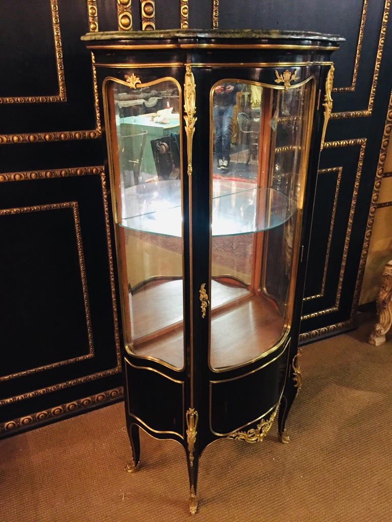 Petite French vitrine in the style of Louis XV Rococo Piano black polished veneer on solid beechwood high-octagonal, one-armed, curved body, three-sided to three-section, on tall, slanting, curly feet. Profiled cornice with marble top. Inside two