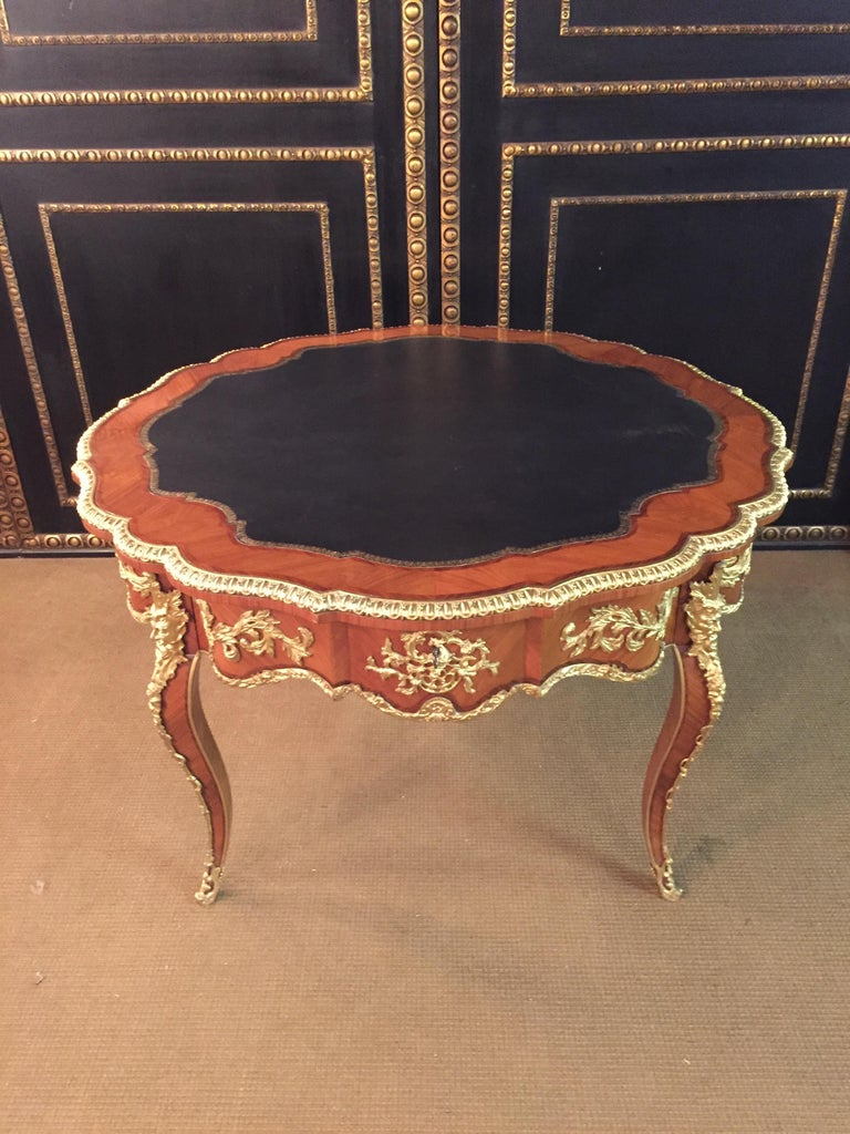 Majestic French salon table in Louis XV style. Polished veneer on solid pinewood. Exceptionally finest engraved, decorative broken rocailles, inlaid with acanthus, and flowered details. On two forward looking imposing bearded devils masks on curved