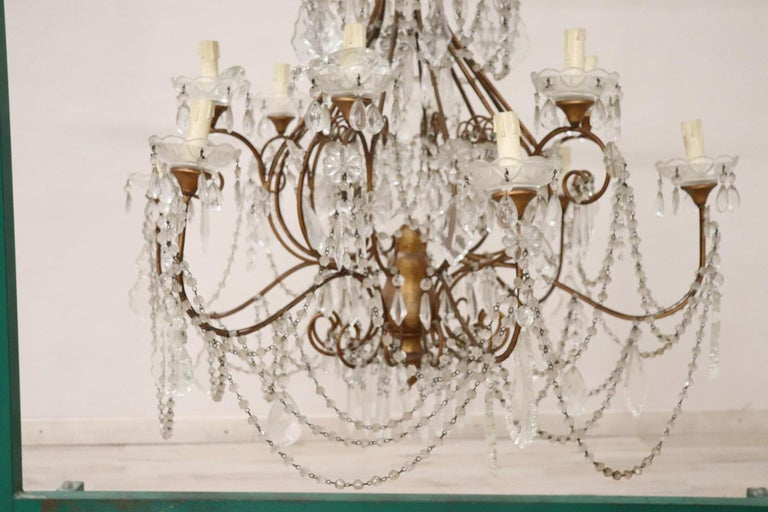 Beautiful and refined Italian Louis XVI style, circa 1940s chandelier eight lights. In gilded bronze and completely covered drops of crystal. The crystal exudes the typical brightness; the drops are finely worked giving an elegant light. The