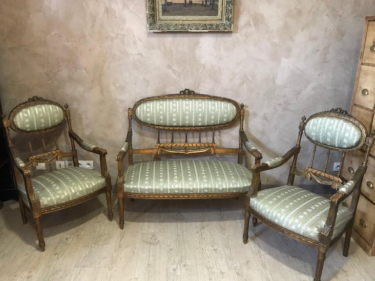 Very nice 20th century French Louis XVI style golden wood and green silk Salon from the 1920s. A sofa, two armchairs and two chairs. Good main condition but some flaws: - Missing glans on the sofa and one on an armchair - An armchair foot has