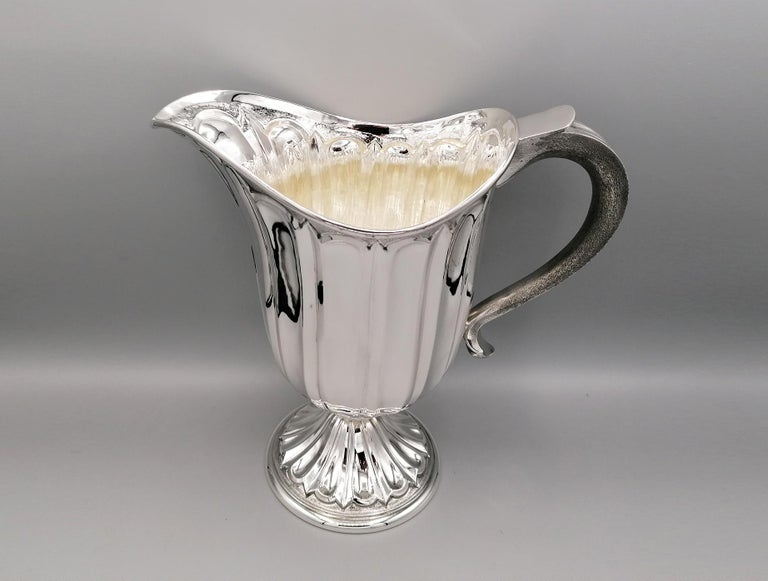 Fully handmade medieval style solid sterling silver jug. The body is oval and shaped embossed grooves. The base, separated from the rest of the body by a bushing, is round with the same design.