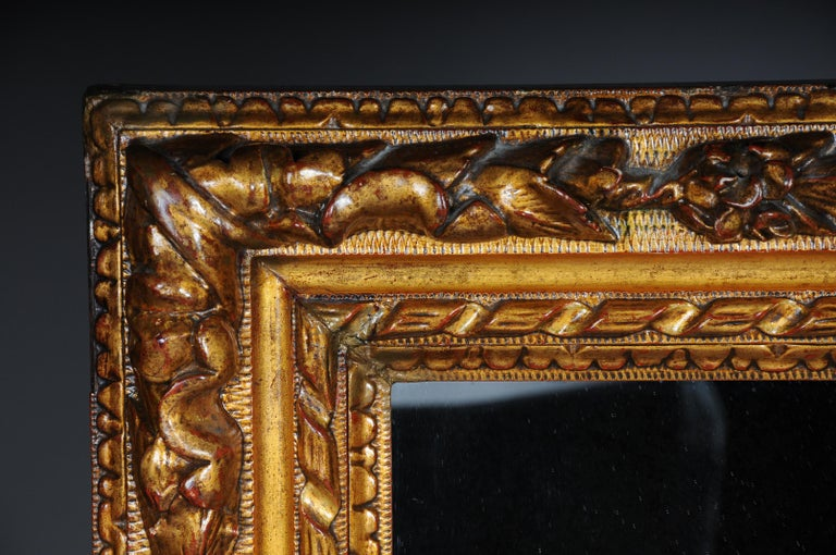 Mirror framed with a richly ornamented baroque frame. Frame completely set in gold.