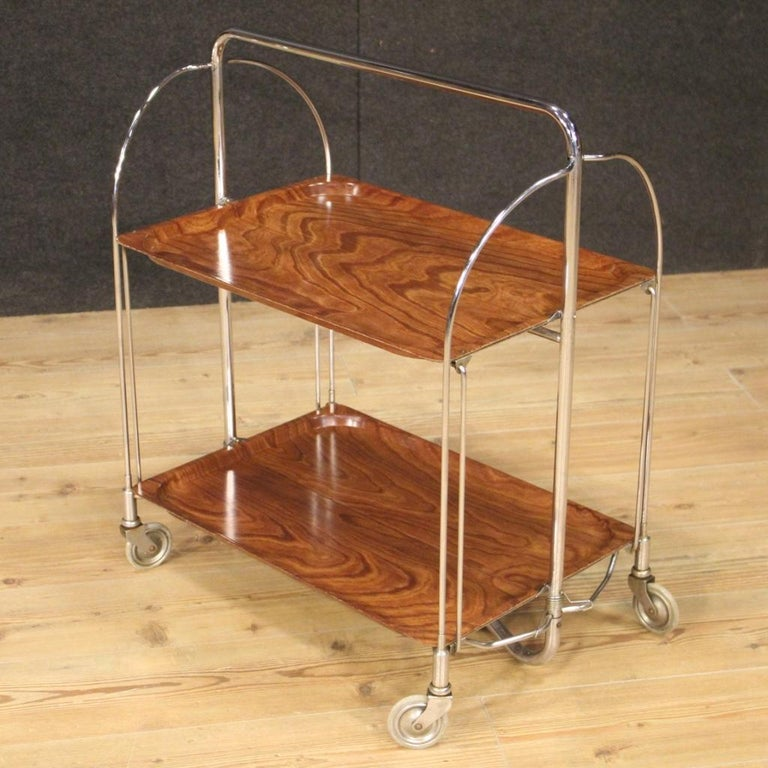 German design service cart from the 1970s-1980s. Metal furniture with two plastic shelves decorated with fake wood of beautiful line and pleasant decor. Cart resting on wheels that once closed occupies a depth of 8 cm. Furniture for interior