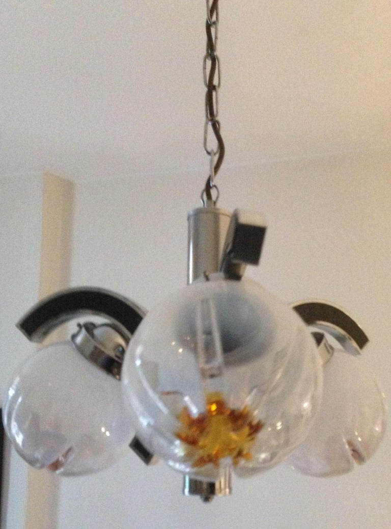 Mid-Century Modern Murano Glass Mazzega chrome and glass chandelier. Fantastic Mazzega Murano glass and chrome ceiling pendant light. This beautiful light fixture will grace any area of your home with subtle warm light. The glass is handblown and
