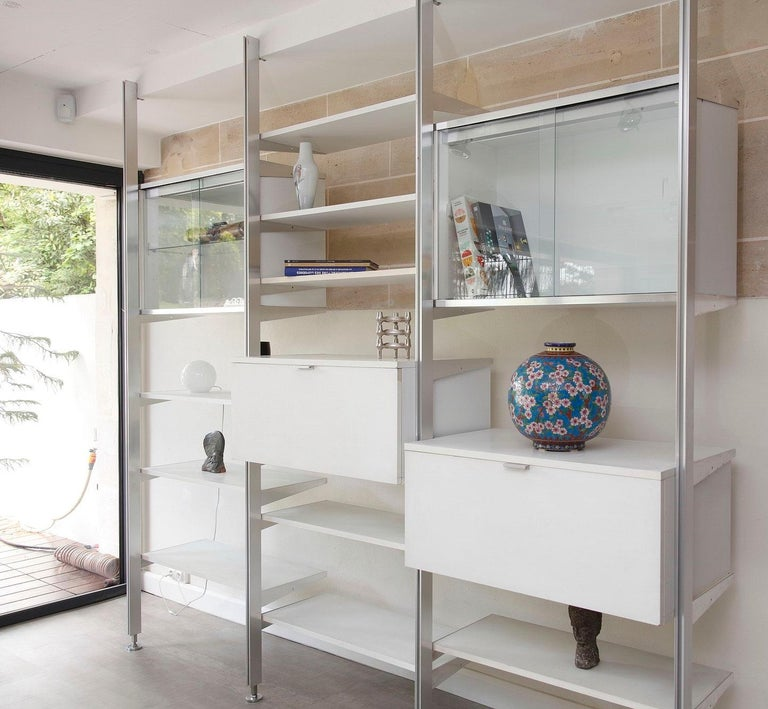 Vintage modular wall unit crafted in white lacquered wood and stainless steel. This wall shelf model known as Comprehensive Storage System (CSS), was made by Georges Nelson in the late 1950s and manufactured by Mobilier International in the