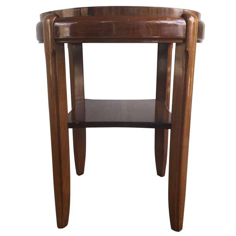 A vintage Art Deco Italian round side table made of hand carved mahogany with a brown leather top, in good condition. Wear consistent with age and use, circa 1930, Italy.